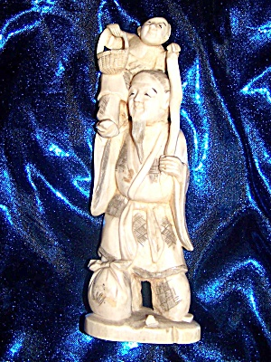 Ivory Figurine Of Oriental Man Holding Child.