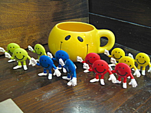 Twelve M&m Figures In A Yellow Happy Face Cup